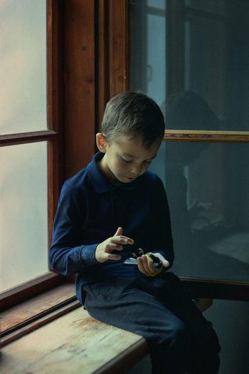 Rear view of boy looking through window