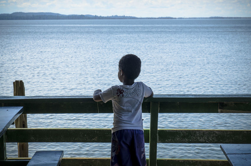 A boy looks to a river in Amazon / Brazil. Amazon Amazonas Blue Brazil Calm Child Contemplation Dream Nature Nature Poverty River Stare Third World Tranquility Water