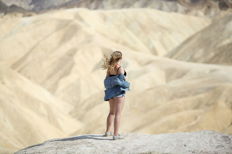Young girl in casual clothing overlooking Zabriskie Point, the most famous viewpoint in the Death Valley National Park, USA Death Valley Photoshoot USA Zabriskie Point Adult Beautiful Woman Beauty In Nature Casual Clothing Full Length Girl Hairstyle Leisure Activity Lifestyles Model One Person Outdoors Real People Rear View Rock Rock - Object Rock Formation Standing Women Young Adult Young Women
