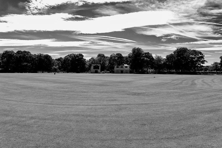 Howzat. Cricket Field Beauty In Nature Black And White Clean Cloud - Sky Cricket Cricket Club House Day Empty Environment Field Grass Land Landscape Nature No People Outdoors Scenics - Nature Sky Sport Summer Sunlight Tranquil Scene Tranquility Tree