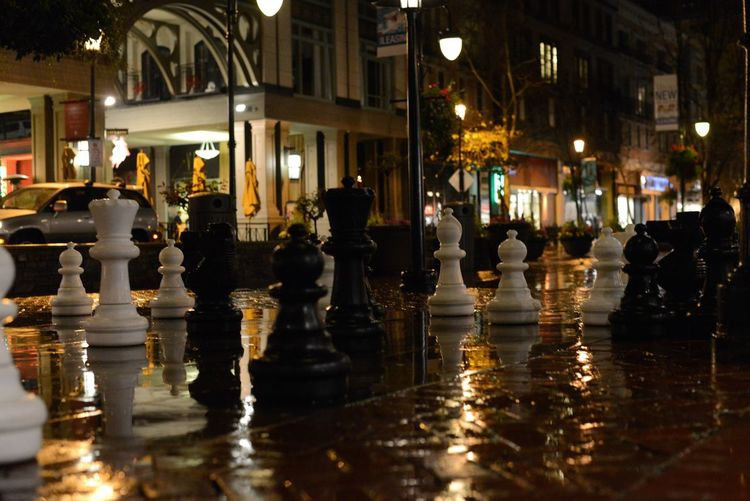 Chess pieces on city street at night