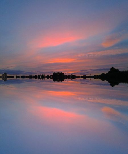 Idyllic shot of sunset sky reflection in lake