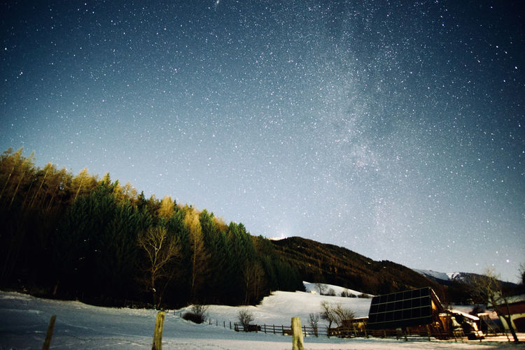 Scenic view of snow covered land against sky at night