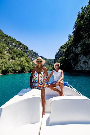 Full length of couple sitting in boat in lake