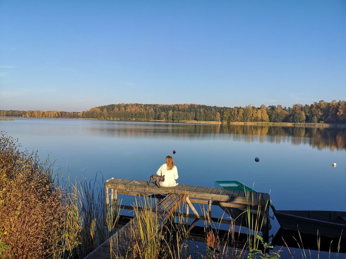 Rear view of woman with dog relaxing on lake pier against clear sky