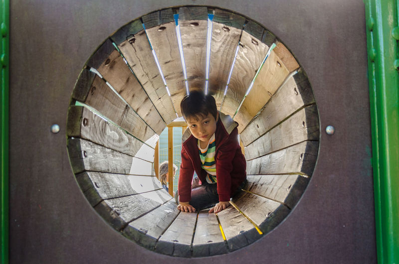 A young boy crawls through a tunnel in a children's playground. Boy Child Children's Playground Circle Close-up Crawl Crawling Fun Person Playground Through Tunnel Wooden Tunnel Young