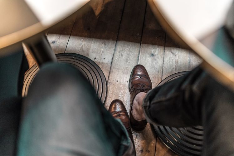 Low Section Of Man Wearing Shoes On Wooden Floor