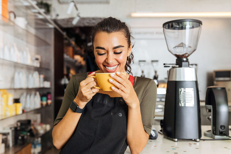 Young woman holding coffee cup in cafe