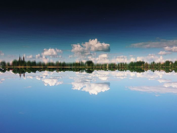 Scenic view of lake by buildings against blue sky