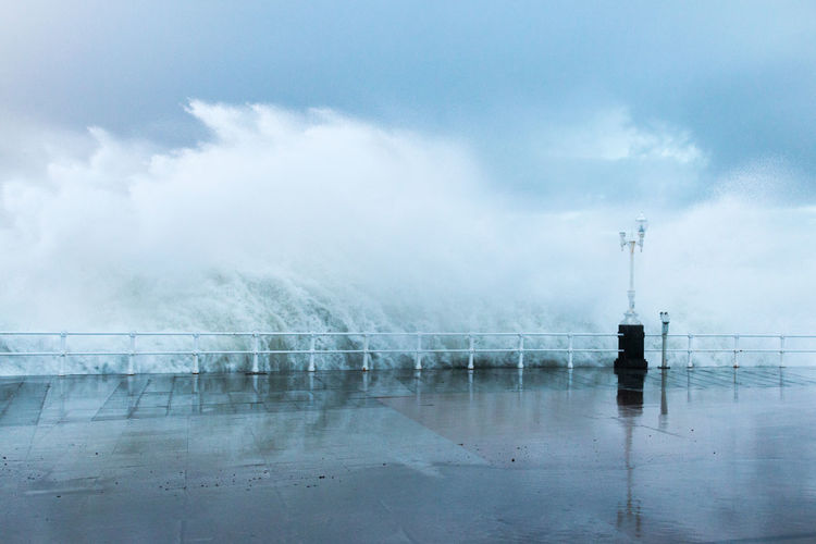 Scenic view of wave splashing  against sky during rainy season