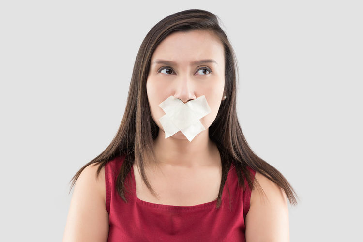Asian women in red dresses use masking tape to close the mouth because they do not want to comment on a gray background, Thai female in with adhesive tape over his mouth, Stop talking Speaking Stop Speech Close Mouth Speak
