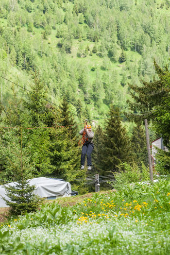 Woman Riding Zip Line Over Field Against Mountains