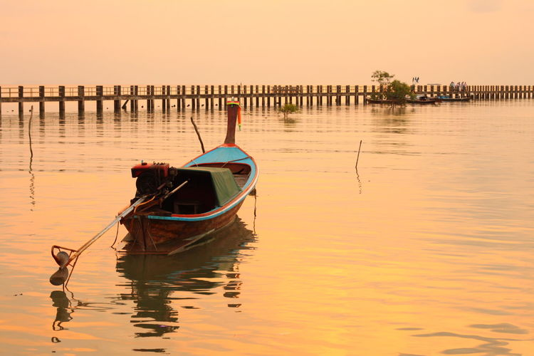 Longtail boat moored on lake against sky during sunset