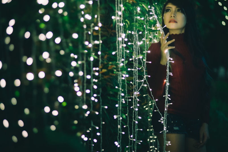 Young Woman Standing By Christmas Lights