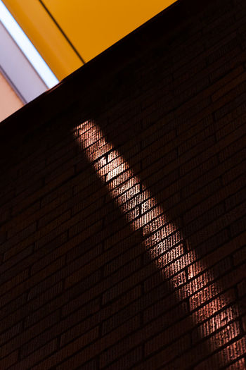 sunlight goes through gap between sunshade and projects on brick wall. Colors Go Through Leakage Sunlight Textures Wall Abstract Architecture Bricks Built Structure Contrast Diagonal Lines Gap Light And Shadow Projection Sky Sunshade Yellow
