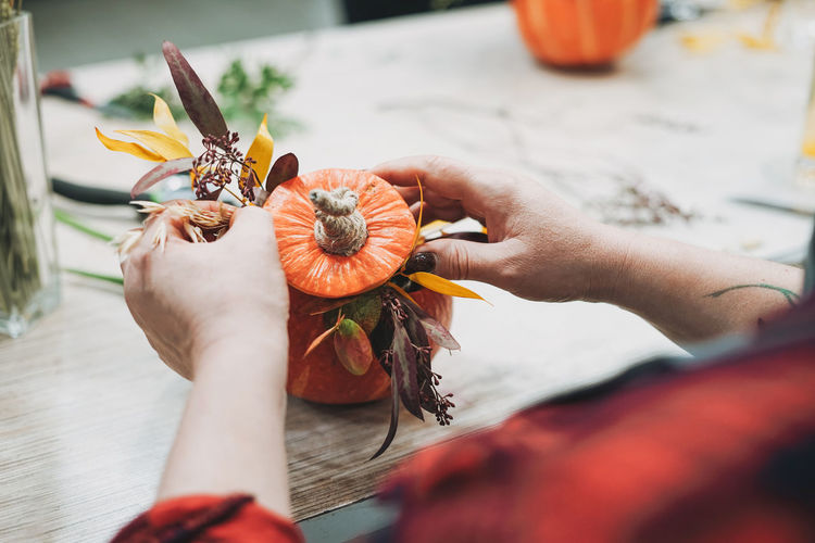 Cropped image of woman decorating pumpkin