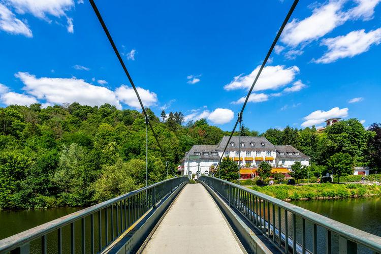 Footbridge over plants against blue sky