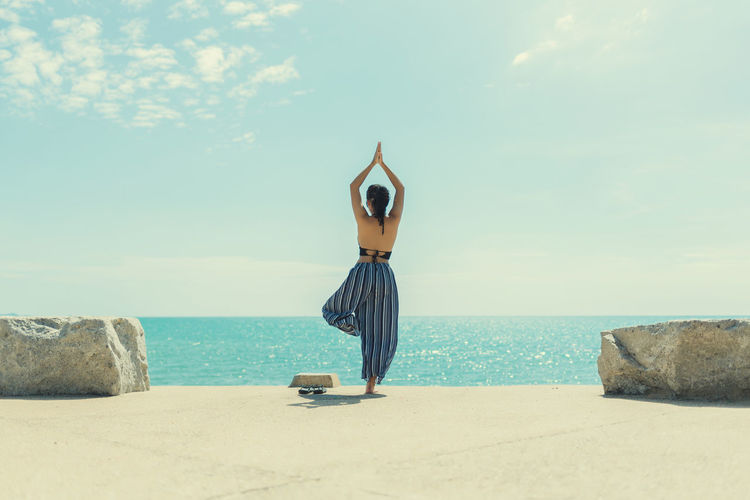 Rear view of woman practicing tree pose yoga at promenade by sea