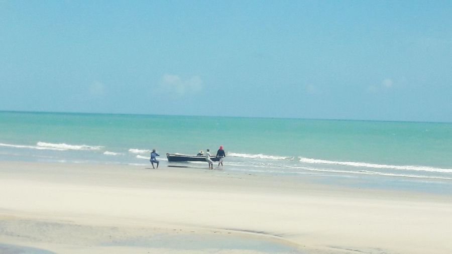 People Pulling Rowboat From Sea On Shore At Beach Against Sky