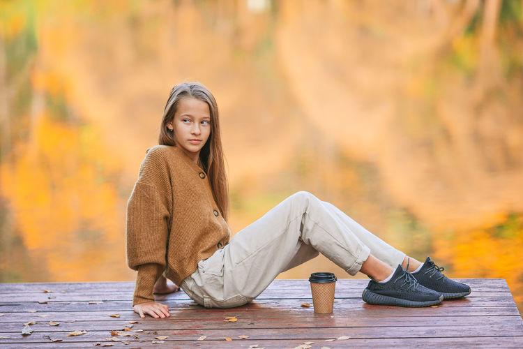 Portrait of teenage girl sitting on wood during autumn
