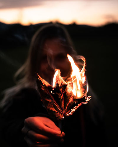 Close-up of woman holding burning leaf at sunset