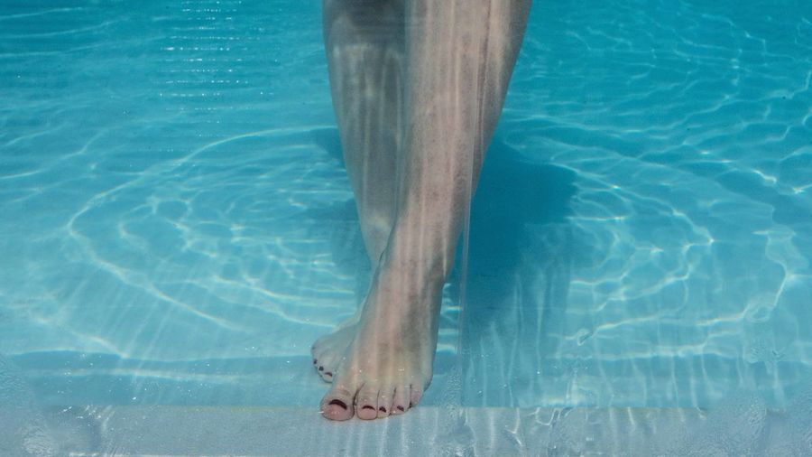 Low section of person standing in swimming pool