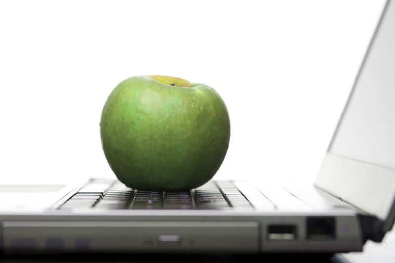Green apple resting on the keyboard of an open laptop computer in an education and healthy eating concept, low angle against a white background Apple Closeup College Computer Conceptual Distance Learning Education Food Fresh Green Healthy Healthy Eating Information Internet Keyboard Laptop Learning Low Angle View Mobility Still Life
