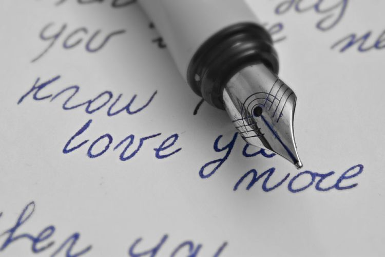 Close-up of fountain pen on text written paper