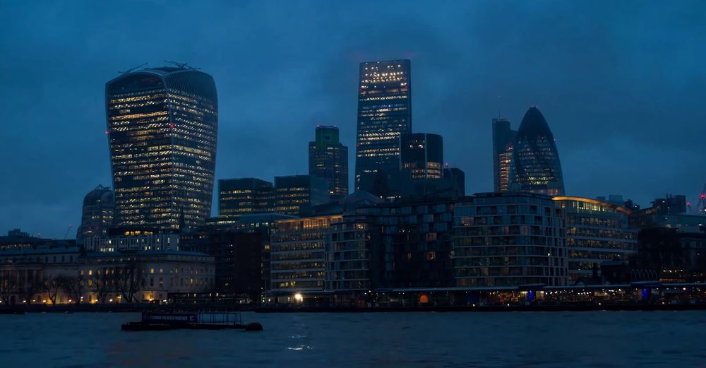 Illuminated buildings in city by river against sky at dusk