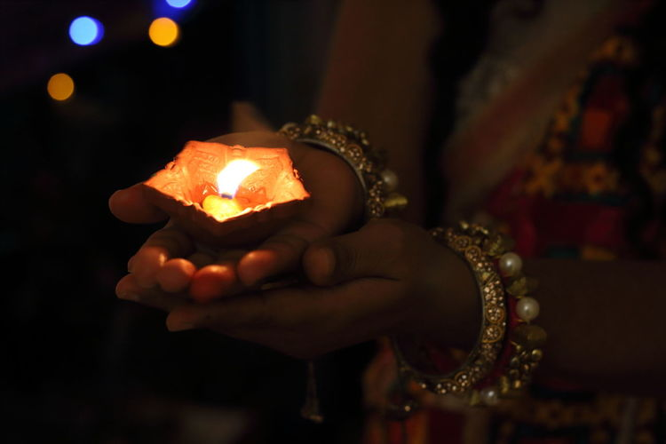 Diwali festival of lights India. festive season of deepawali and festival enjoyment. Hindu festival of lights. One Person Human Hand Hand Holding Jewelry Focus On Foreground Close-up Indoors  Human Body Part Adult Bracelet Night Celebration Bangle Midsection Burning Electric Lamp Luxury