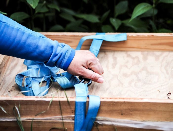 Cropped hand holding blue strap on wooden box