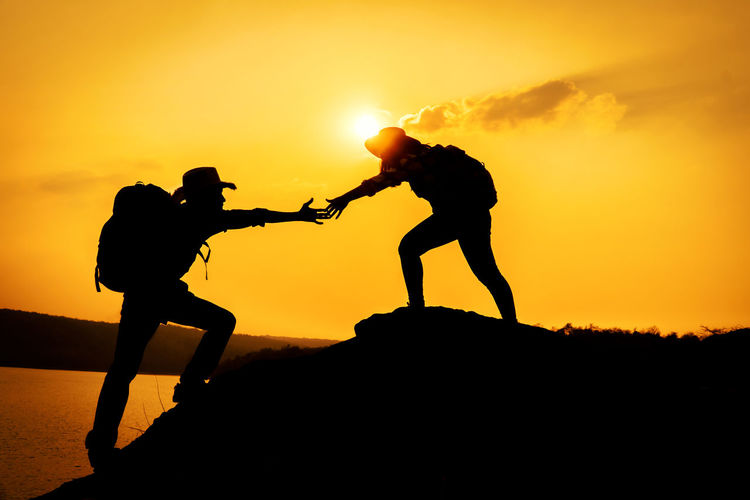 Silhouette Sunset Sky Real People Nature Lifestyles Togetherness Standing Leisure Activity Helping Climbing Mountain Challenge 17.62°