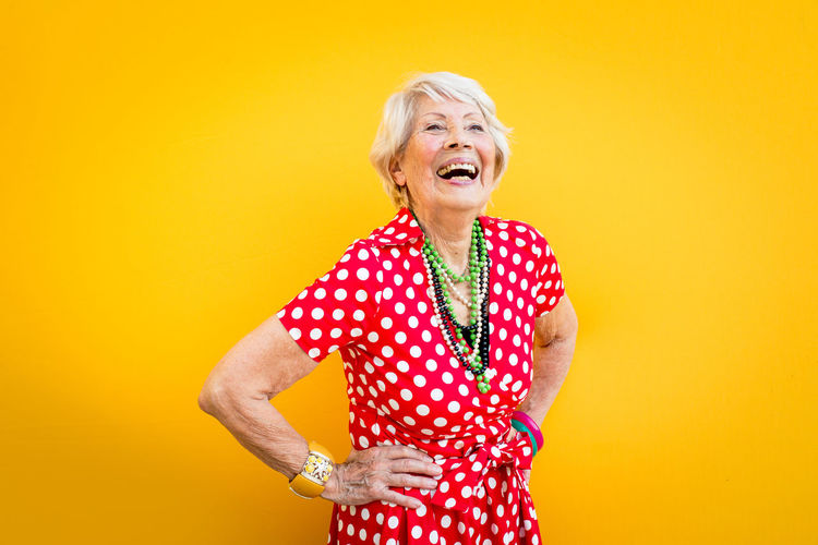 Smiling senior woman standing against yellow background