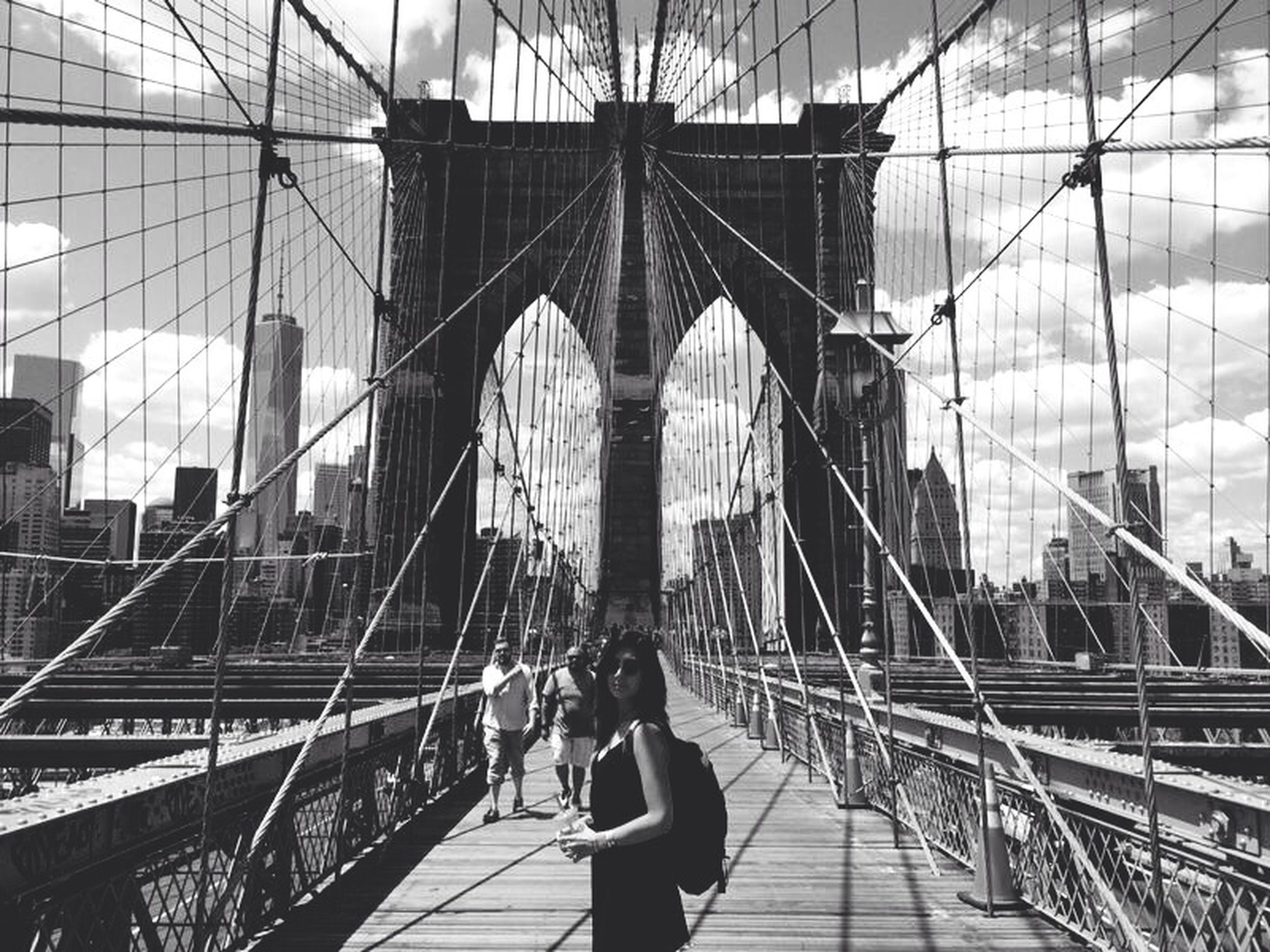 architecture, built structure, bridge - man made structure, lifestyles, connection, men, transportation, person, travel, leisure activity, walking, famous place, suspension bridge, engineering, city, brooklyn bridge, travel destinations, tourism, city life