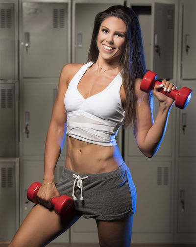 Portrait Of Young Woman Holding Dumbbells While Standing In Locker Room