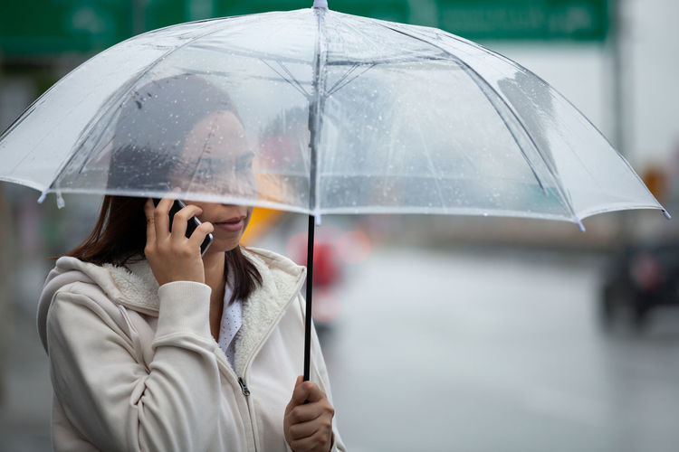 Woman talking on phone while standing with umbrella