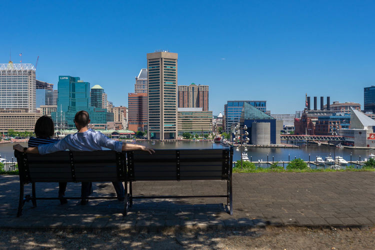 Rear view of couple sitting on bench in city against clear sky