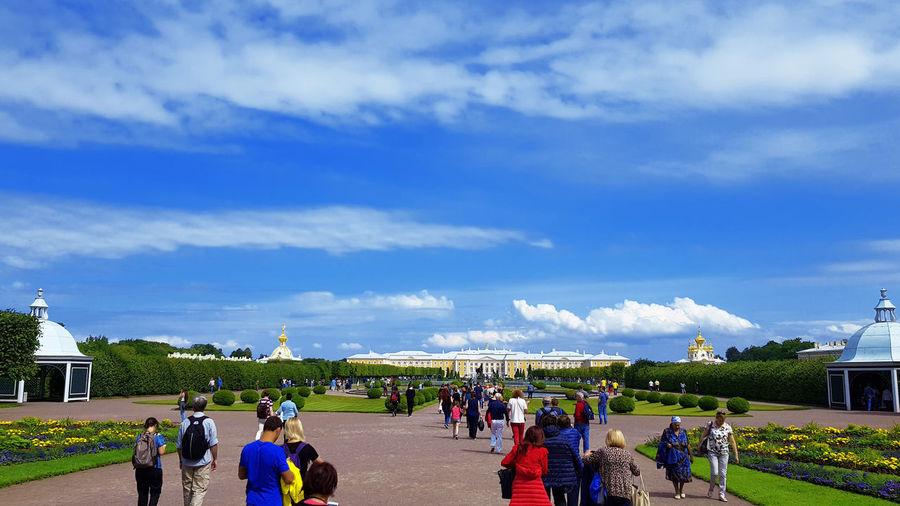 Group of people walking in city against sky