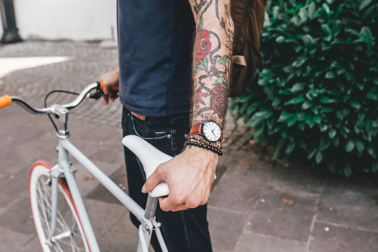 Young Man with tattoos in the street with bicycle Bicycle Real People One Person City Street Lifestyles Day Transportation Casual Clothing Focus On Foreground Men Outdoors Low Section Footpath Standing Human Body Part Human Leg Land Vehicle Sidewalk Human Limb Watch Wrist Watch Jewellery Jewelry Young Adult Young Men City City Life Urban
