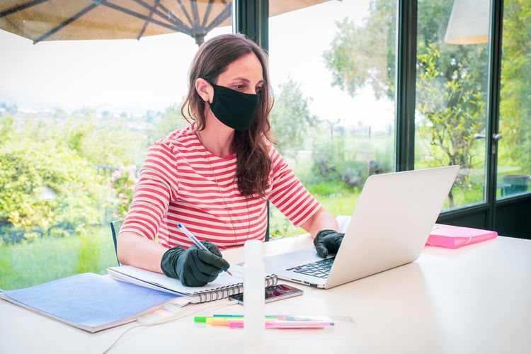 Mature woman wearing mask working at home
