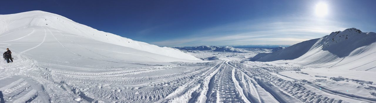 Tire Tracks Amidst Snowcapped Mountains Against Sky
