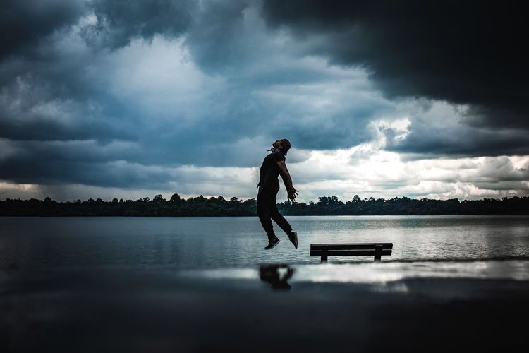 Man jumping over lake against cloudy sky