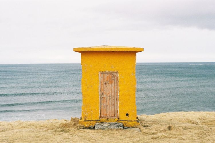 Close-up of yellow hut on beach against sky