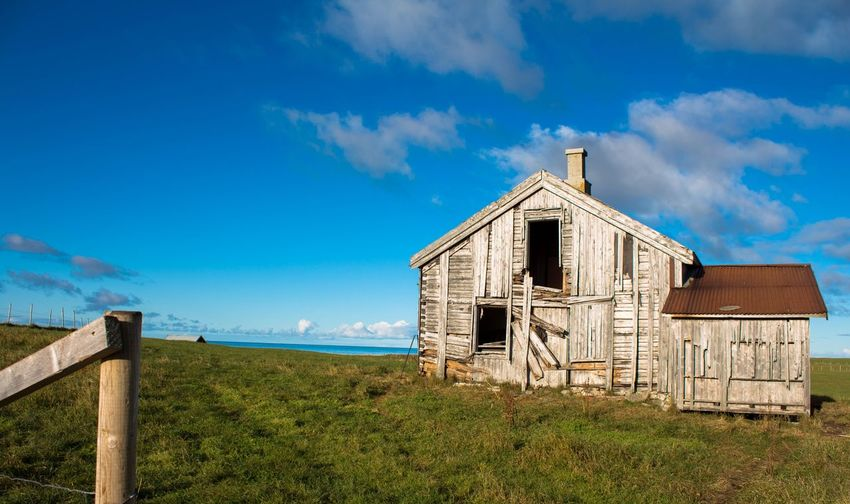 Old house on field against blue sky