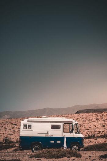 Vintage car on desert against sky