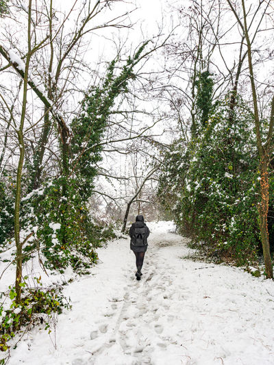 Rear view of person walking on footpath during winter