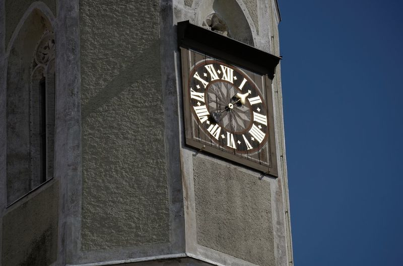 Low angle view of clock tower against clear blue sky on sunny day