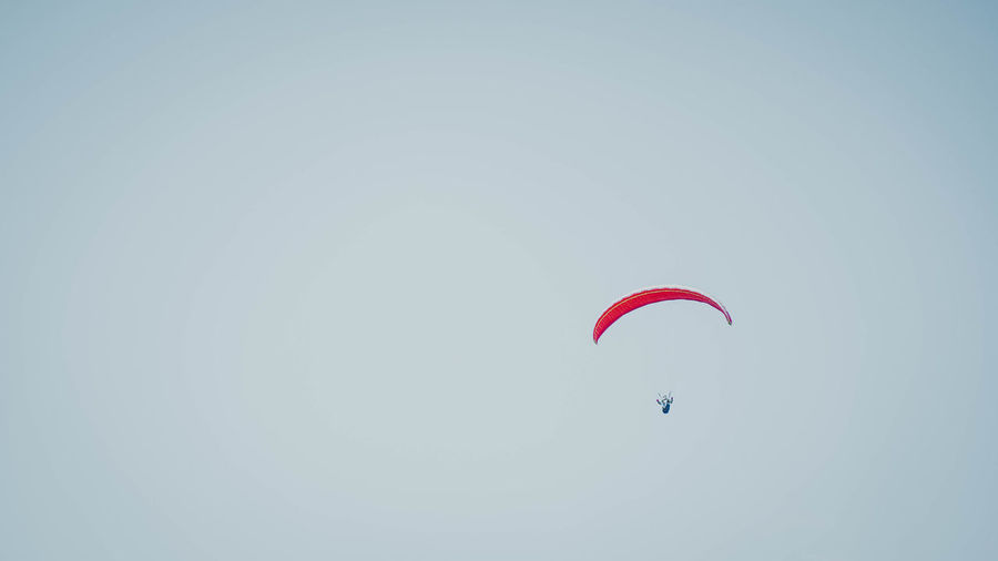 Sport Extreme Sports Paragliding Flying Parachute Unrecognizable Person Adventure Mid-air Low Angle View Sky Real People Leisure Activity One Person Clear Sky Copy Space Lifestyles Day Gliding Freedom Excitement