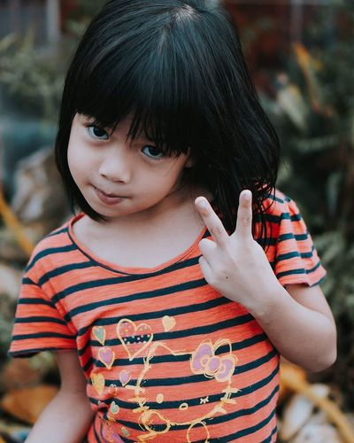 Portrait Of Cute Girl Showing Peace Sign