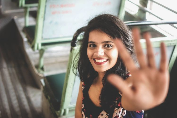 Portrait Of Smiling Young Woman Gesturing While Sitting In Bus